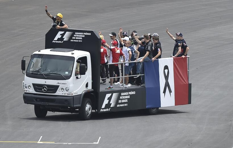 Corredores de Formula 1 desfilan a bordo de un camión con una ban...