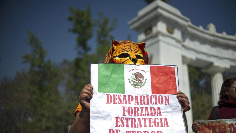 Una persona enmascarada en una manifestación por Ayotzinapa