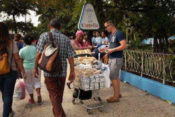 Un vendedor ambulante vende panes de dulce afuera de la heladería...