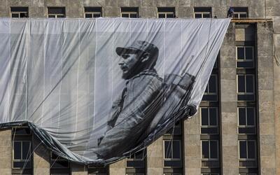 Varios hombres colocan un gran cartel con la imagen del fallecido líder...