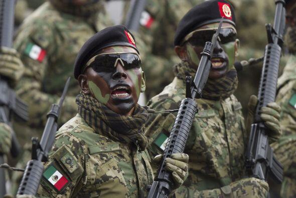Un grupo de militares marchan con sus rifles en mano, gorras negras, len...