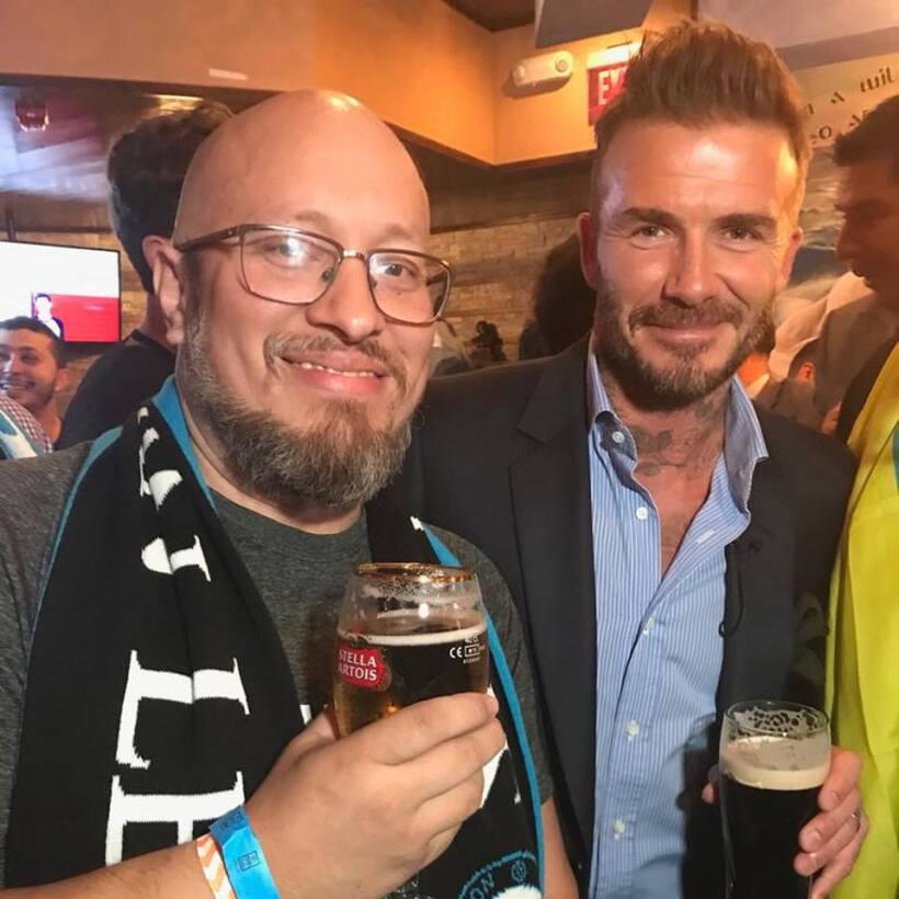 David Beckham celebrating with soccer fan Ed Serrano with Miami's &q...
