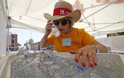 Una mujer se refresca el intenso calor en Phoenix