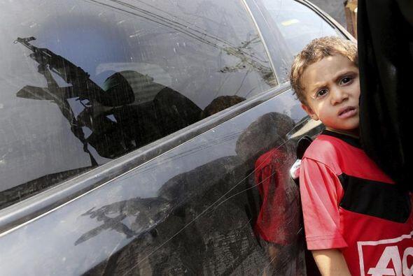 Una mujer portando un rifle Kalashnikov se refleja en la ventanilla de u...