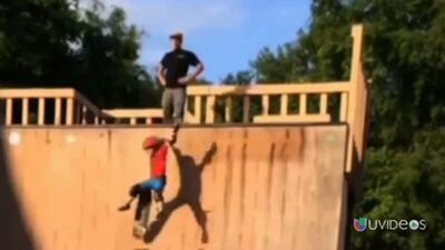 Padre empuja a su hijo a una rampa con todo y patineta