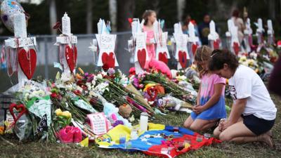 Personas visitan el memorial en frente de la escuela secundaria Marjory...