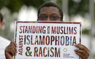 """El manifestante Gregory Saint-Jean sostiene un cartel que lee """"De pie co..."""