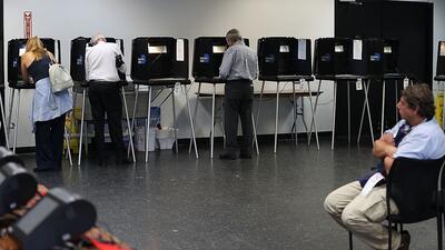 Votantes de la Florida se acercan a las urnas de votación para las prima...
