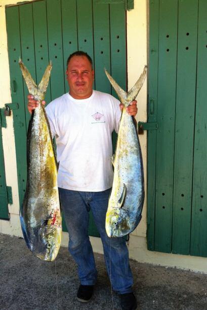 Michael, otro de los pescadores muestra jubiloso sus dorados luego de un...
