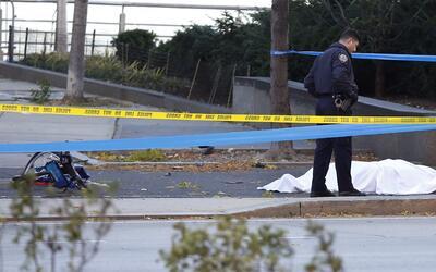 Un oficial de policía al lado de una de las víctimas y a p...