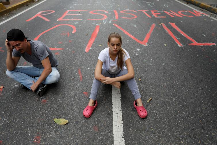 Opposition supporters sit next to graffiti on the street that reads 'Civ...