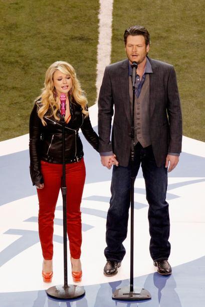 Miranda Lambert y Blake Shelton tomados de la mano en medio de la cancha.