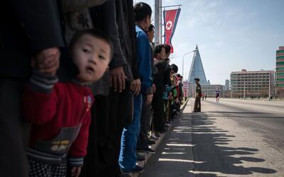 Un niño ve los corredores del marathon de Pyongyang el 9 de abril...