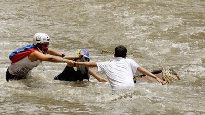 En fotos: los manifestantes venezolanos que se lanzaron a un río putrefacto para protegerse de la represión
