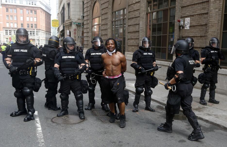 La policía escolta a un hombre que participaba en la contraprotesta a la...