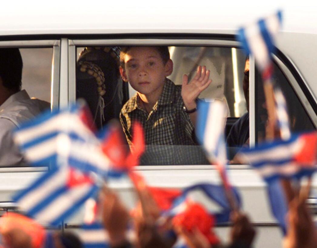 Cuban castaway Elian Gonzalez waves to his fellow school mates on his ar...