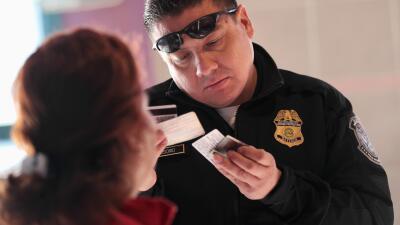 Un agente de inmigración de EEUU revisa los documentos de un inmigrante...