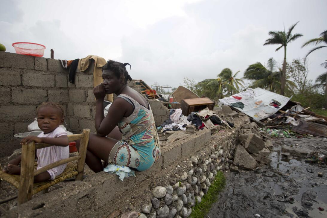 A woman and her daughter in the ruins of their home in Les Cayes, Haití.