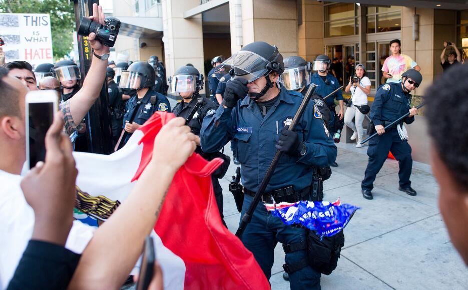 Un policía se protege de la muchedumbre que tiraba objetos en San José, CA.