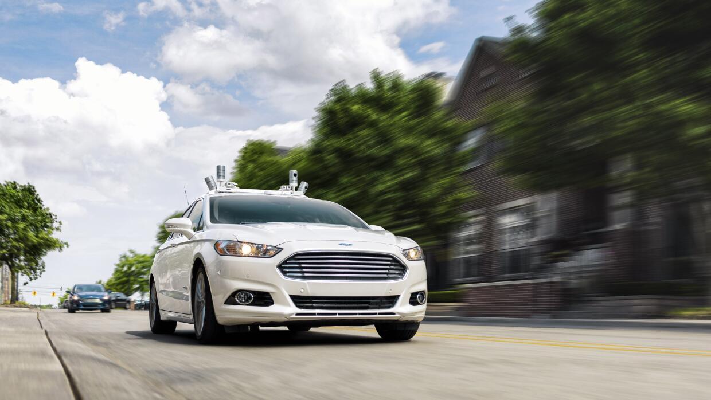 Ford Fusion de manejo autónomo circulando por las calles de Dearborn en...