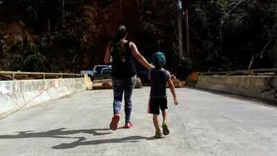 Una madre camina con su hijo por un puente roto por el huracán María en...
