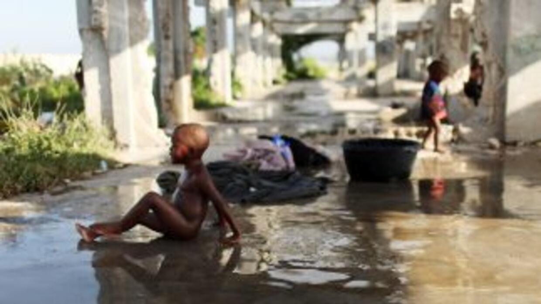 Un pequeño toma un baño en uno de los campamentos de refugiados en las i...