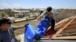 Bob Fiorile, 72, and Todd Brown, 42, right, pull a tarp onto the exposed...