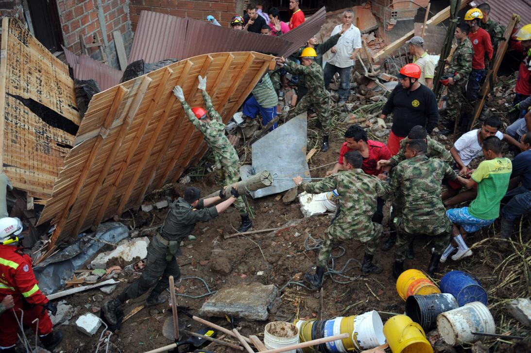 Colombian soldiers, policemen, firefighters and locals help remove rubbl...