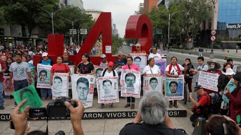 Familiares de los estudiantes de Ayotzinapa desaparecidos posan frente a...