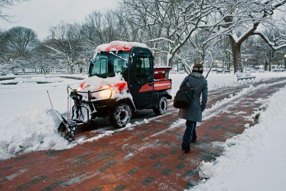 Trabajadores del departamento de parques despejan la nieve para la circu...