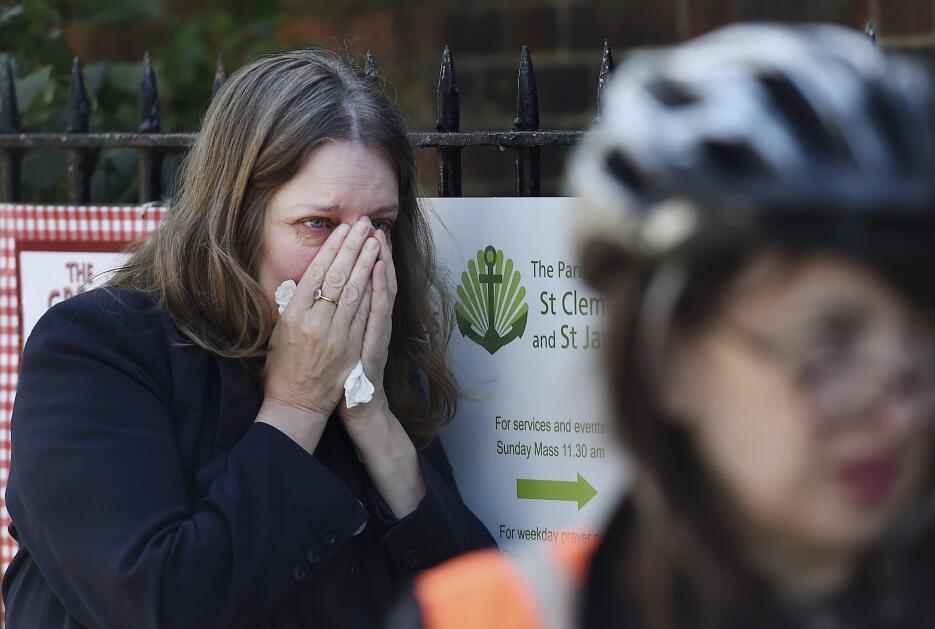 Una mujer llora mientras los bomberos trabajan en las labores de extinci...