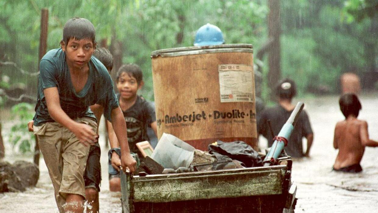 A child drags his belongings down a flooded street October 31,1998, in M...