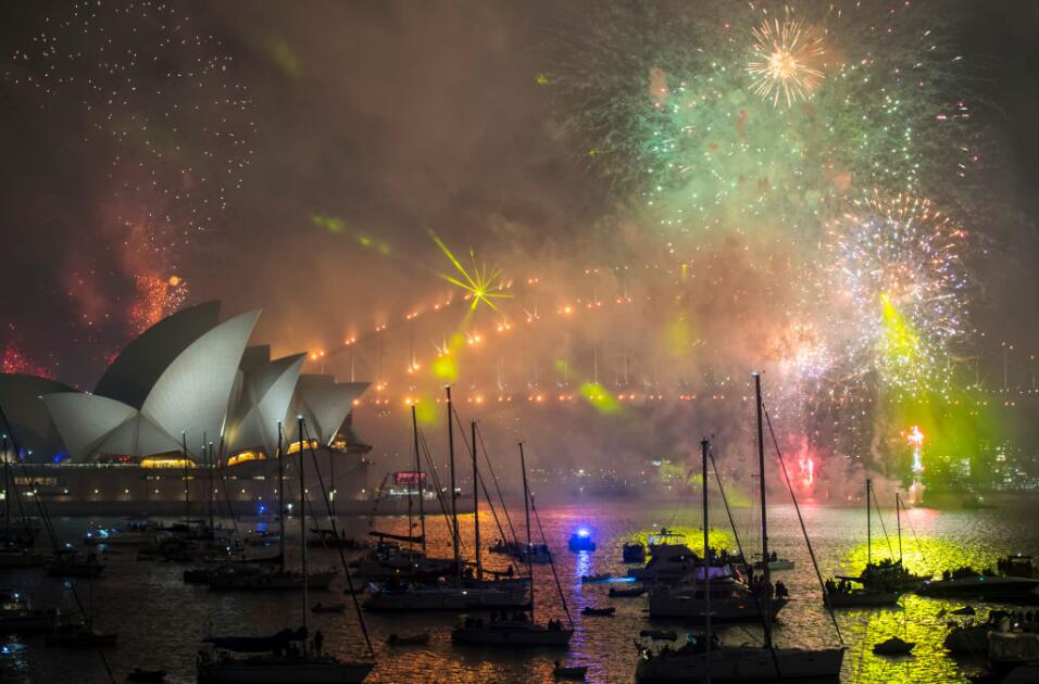 Fireworks explode off the Harbour Bridge and Opera House to bring in the...