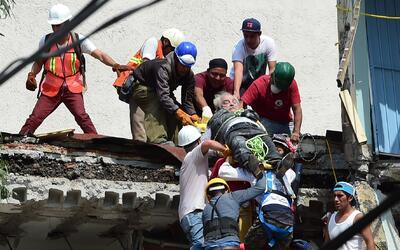 Rescatistas sacan de los escombros de un edificio colapsado a una person...