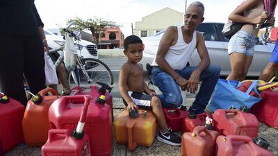 Un niño acompaña a su tío a buscar gasolina en Carolina, tras el paso de...