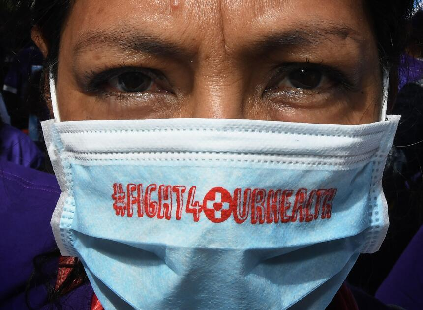 A protester dressed as a hospital patient marches towards the Federal Bu...