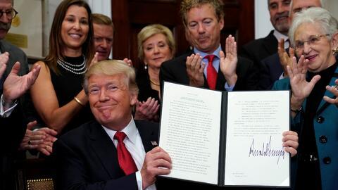 El presidente Trump sonríe al firmar una orden ejecutiva que perm...