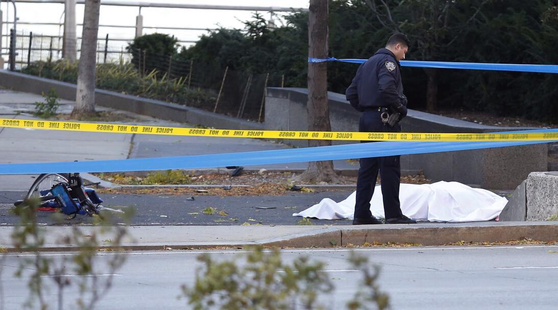 Un oficial de policía al lado de una de las víctimas y a poca distancia...