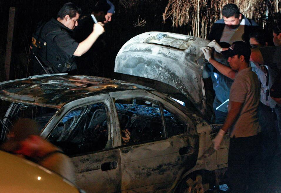 Detectives revisan un vehículo quemado con seis cadáveres...