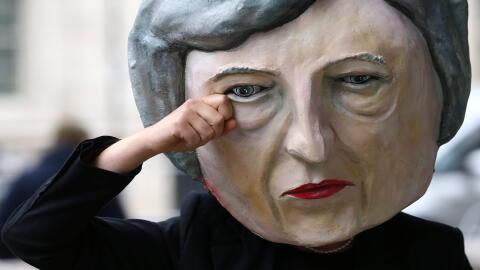 Una mujer protesta este viernes delante de Downing Street con una careta...