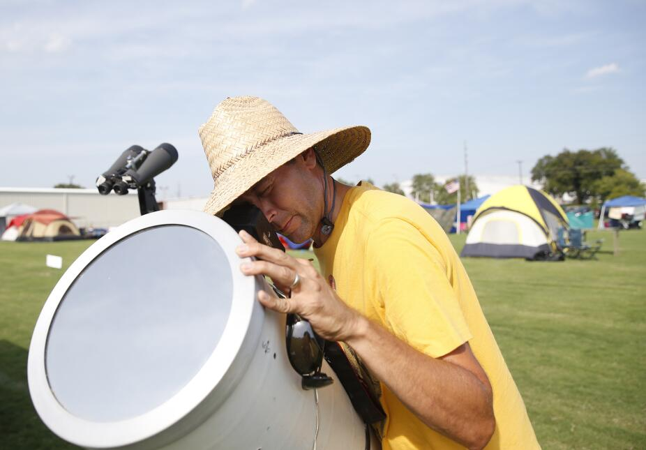 Brian Badgett coloca su cámara dentro de un telescopio para fotografiar...