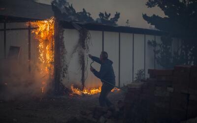 Un hombre intenta apagar una estructura incendiada por el fuego Creek, q...