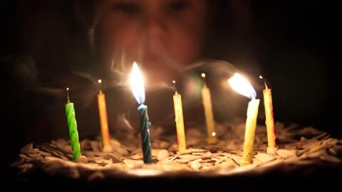 Niña sopla la torta de cumpleaños