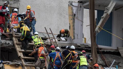 Un grupo de rescatistas continúan buscando a personas con vida en los de...