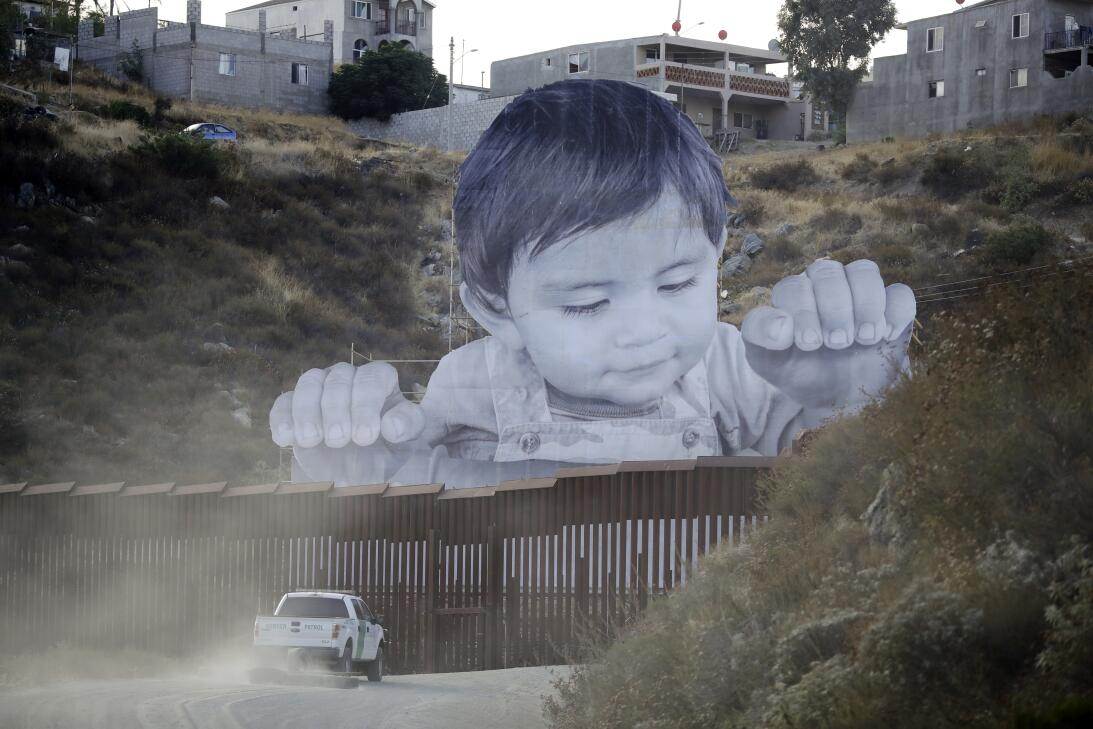What is this curious child thinking as he peers over the border wall? Pi...