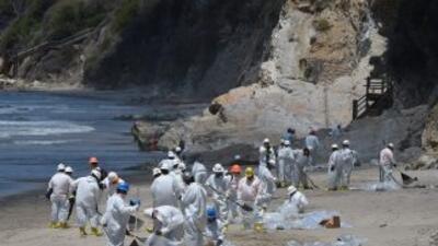 Trabajadores limpian una de las playas afectadas por el derrame de petró...