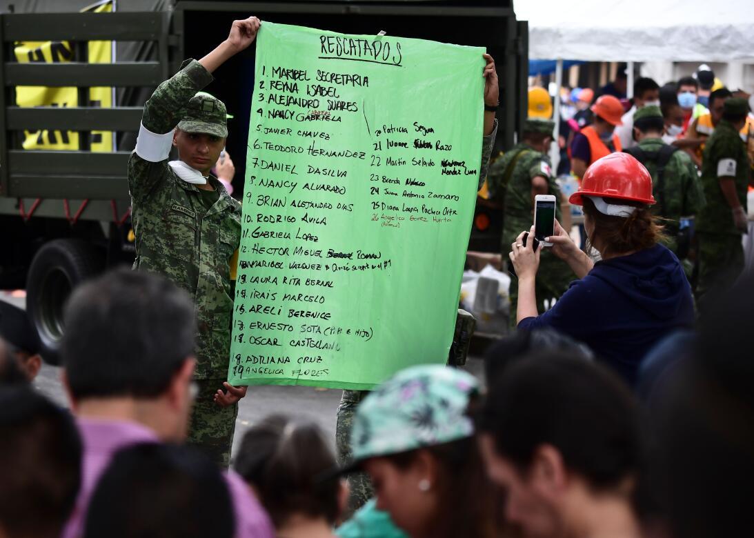 Un soldado muestra una lista de rescatados informal, cerca de uno de los...