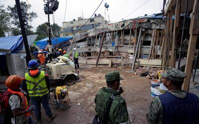 Soldados y trabajadores de rescate entre los escombros de la escuela Enr...