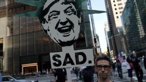 Un manifestante sostiene una pancarta en contra del presidente Donald Tr...