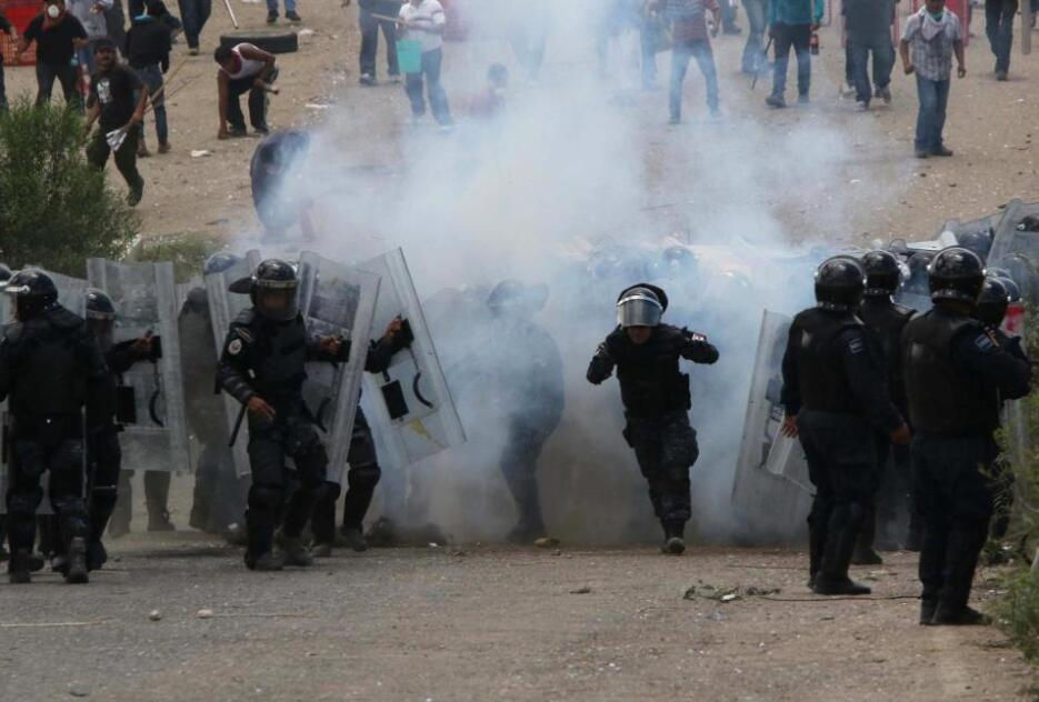 Teachers and police officers amidst a cloud of tear gas